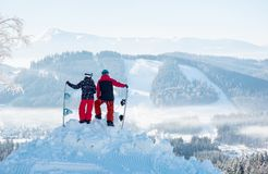 Two snowboarders enjoy the snow-white scenery of mountains and forests royalty free stock photos