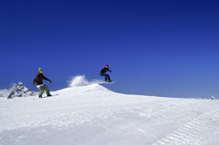 Two snowboarders jump in snow park at ski resort on sunny winter stock photo