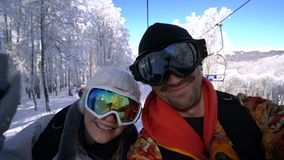 Two snowboarders on a lift makes selfie. Sunny day stock video footage