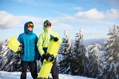 Two snowboarders posing at ski resort. Riders friends carrying their snowboards through forest for backcountry freeride stock images