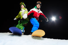 Two snowboarders ready to slide at night Royalty Free Stock Images