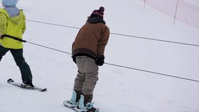 Two snowboarders ride on slope at snowy mountain. Contest. Challenge. Uniform. Rope. Sunglasses. Slow motion stock video