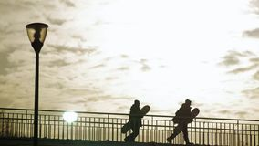 Two snowboarders run across the bridge at sunset. Snowboarders cross the bridge on the sunset sky background stock video footage