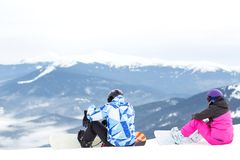 Two snowboarders are sitting on a high mountain slope. Mountain tops in the snow, panorama of mountain slopes and hills at sunset Royalty Free Stock Photos
