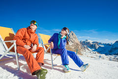 Two snowboarders on top of the mountain having fun sitting on chair chaise lounge Royalty Free Stock Images