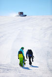 Two snowboarders walking up a slope Royalty Free Stock Photo
