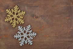 Two snowflakes on a wooden board Stock Photos