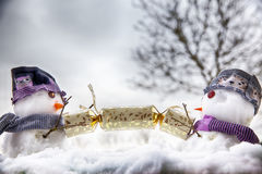Two snowman characters pulling a Christmas cracker Royalty Free Stock Photos