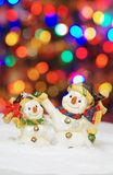 Two snowman with christmas lights in the background Royalty Free Stock Photo
