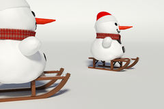 Two snowman,and wooden sleds with him Royalty Free Stock Images