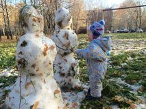 Two snowmen and baby. Baby holding hands with two snowmen Stock Photos