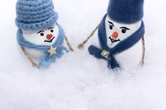 Two snowmen in a blue hat and scarf are standing in a snowdrift of snow royalty free stock images