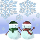 Two snowmen dressed in knitted caps and scarves Stock Images