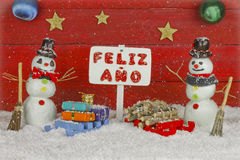 Two snowmen with a Happy New Year signpost with the words written on spanish Stock Photography