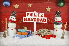 Two snowmen holding a sign with the words Merry Christmas written on spanish Royalty Free Stock Images