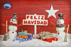 Two snowmen holding a sign with the words Merry Christmas written on spanish Stock Image