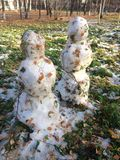 Two snowmen. Are made of snow and leaves Royalty Free Stock Photos