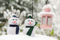 Two Snowmen outdoor. Artificial snowmen in snow outdoor in blue and green Royalty Free Stock Photography