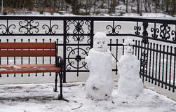 Two snowmen, Park, bench, winter, snow Royalty Free Stock Photography
