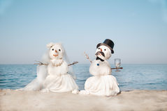 Two Snowmen at the sea Royalty Free Stock Photos