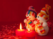 Two snowmen with two burning heart shaped candles Royalty Free Stock Photography
