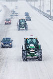 Two Snowplows and Cars During a Snowstorm Royalty Free Stock Photography