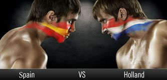 Two soccer fans with flags face to face. Spain and Holland, World Cup 2014 royalty free stock photography