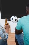 Two soccer fans watching tv. Rear view of two soccer fans watching tv Royalty Free Stock Images