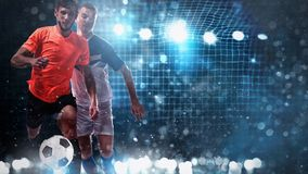 Close up of a challenge between soccer players with a soccer goal in the background. Two soccer players chase the ball at the stadium royalty free stock photos