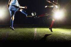 Two soccer players kicking a soccer ball at game Stock Image