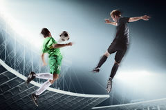 Two soccer players kicking a soccer ball royalty free stock photos
