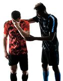 Soccer players men isolated silhouette white background. Two soccer players men in studio silhouette isolated on white background Stock Photography