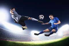 Two soccer players in mid air kicking the soccer ball, stadium lights at night in background Stock Images