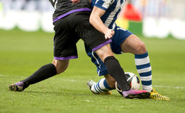 Two soccer players vie. Legs of two soccer players vie on a match Royalty Free Stock Photos