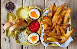 Two soft boiled eggs with fries and sauces. Royalty Free Stock Photo