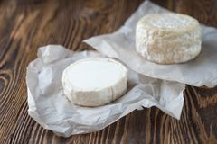Two Soft french cheese of camembert and other types. Two soft round cheese head on paper, rustic natural wooden background stock images
