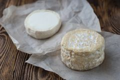 Two Soft french cheese of camembert and other types. Two soft round cheese head on paper, rustic natural wooden background royalty free stock image
