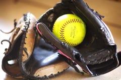 Two softball mitts and a yellow softball. Stock Photo