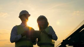 Two solar engineers in the middle of a discussion in the sun rays. 4K stock footage