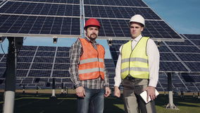 Two solar power engeneers looking in camera. Two of solar panel engineers surrounded by large collector arrays outside looking camera stock footage