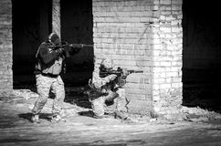 Two soldier in combat gear. black and white. Two soldier in urban building with M4 gun and multicam gear. black and white Stock Photos