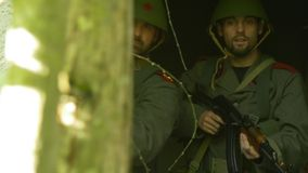 Two Soldiers aiming with AK-47 SU out of a broken window – Moving Camera stock footage