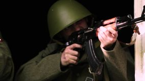 Two soldiers aiming with AK-47 SU out of a broken window stock video footage