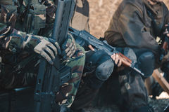 Two soldiers in camouflage and gloves keep the hands in the mach Stock Photos