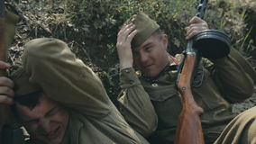 Two soldiers lay in a dugout and hiding from. Two soldiers lay in the dugout and hiding from bullets in wartime stock video footage