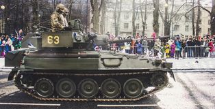 Two Soldiers Ride on Green Military Tank Surrounded With People Stock Images