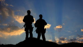 Two Soldiers Silhouette Standing Against Clouds. Two military men stand on a hilltop as the sunsets in front of them stock footage