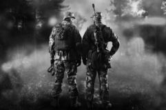 Two soldiers of a special unit are standing in a smoky forest. Mixed media royalty free stock image