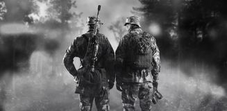 Two soldiers of a special unit are standing in a smoky forest. Mixed media royalty free stock photography