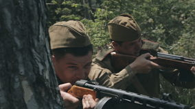 Two soldiers in uniforms and with rifles hiding. Behind tree and fire at enemies stock video